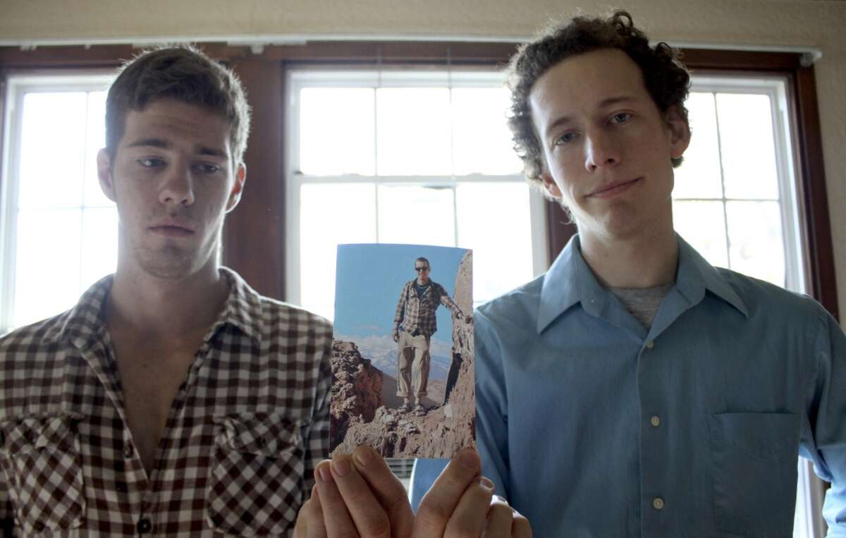 Robert Cameron Redus' brothers Everette, left, and Kris, right, hold a photo of their brother in their home in Baytown, Texas December 10, 2013 showing Cameron when he was in the Atacama desert while on a trip to Chile.