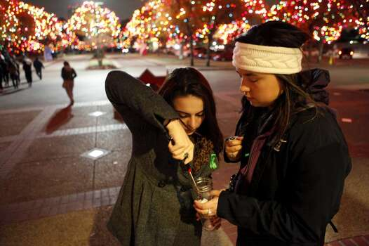 Miriam Thomas (left) tries to light Megan Gaitan's candle Dec. 7, 2013 as they prepare to walk from the University of Incarnate Word Academic Convocation Center to the grotto as a vigil is held for Robert Cameron Redus who was a UIW student shot and killed by an university police officer. Many in attendance either wore green clothing or a green ribbon as it was his favorite color. Photo: FOR THE SAN ANTONIO EXPRESS-NEWS