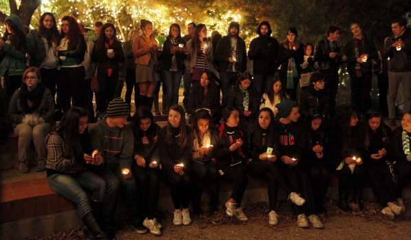 A vigil is held Dec. 7, 2013 for Robert Cameron Redus who was a University of the Incarnate Word student shot and killed by an university police officer. The vigil began at the UIW Academic Convocation Center and then finished at the grotto. Many in attendance either wore green clothing or a green ribbon as it was his favorite color. Photo: FOR THE SAN ANTONIO EXPRESS-NEWS