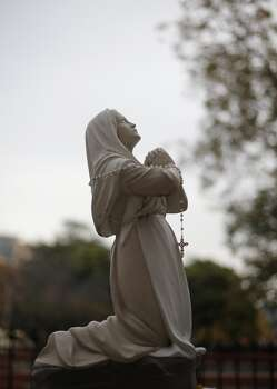 A rosary hangs on a statue near a memorial on the University of the Incarnate Word campus for senior Robert Cameron Redus, Wednesday, Dec. 11, 2013, in San Antonio.  Redus, 23, was shot and killed by a campus police officer on Friday. (AP Photo/Eric Gay) Photo: Associated Press