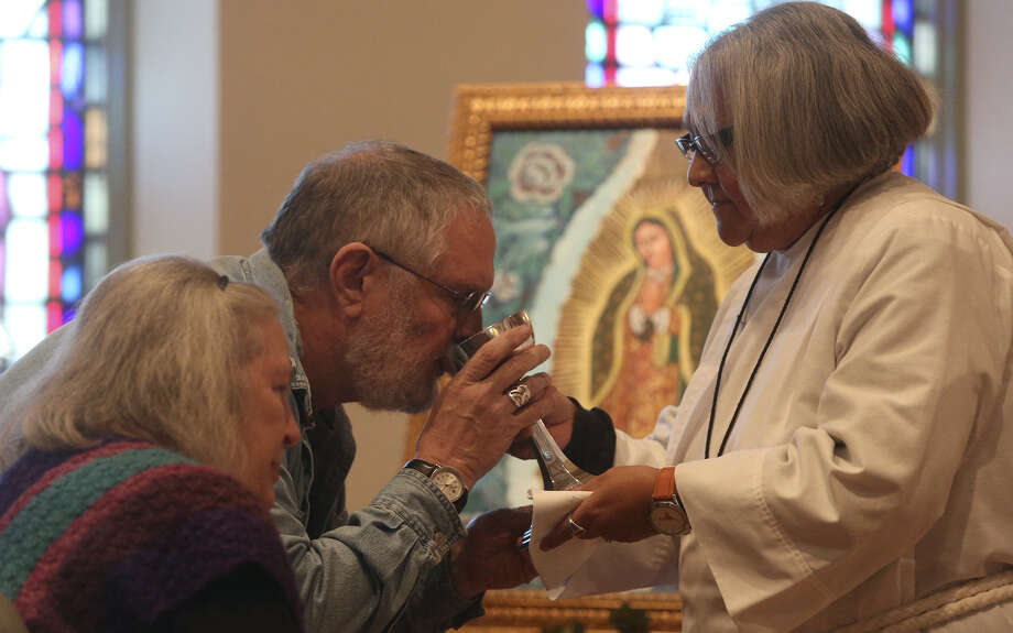 Enedina Vasquez, a former Catholic turned Episcopal lay preacher, gives communion to George and Connie Butchee after speaking about Our Lady of Guadalupe during a Mass at St. Paul's Episcopal Church. She spoke a day before Our Lady of Guadalupe's feast day. Photo: Lisa Krantz / San Antonio Express-News / FOR THE SAN ANTONIO EXPRESS-NEWS