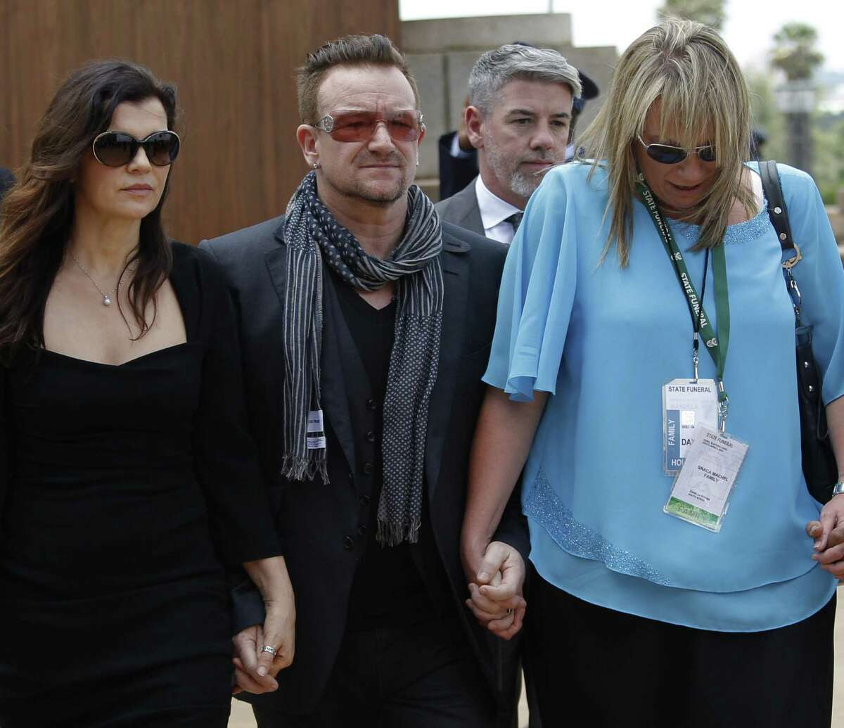 Bono and his wife, Ali Hewson (left), and Nelson Mandela's former assistant, Zelda le Grange, leave after paying their respects.