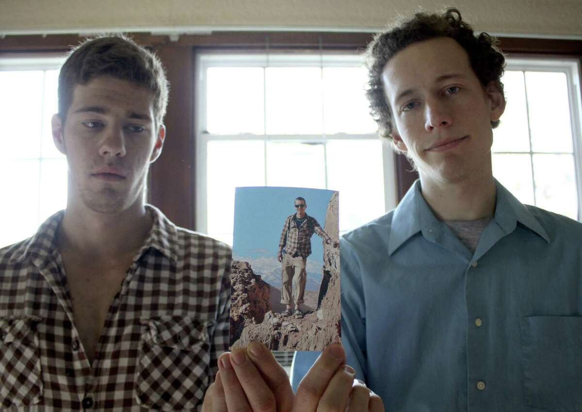 Robert Cameron Redus' brothers Everette (left) and Kris hold a photo of their brother in the Atacama desert while he was on a trip to Chile.