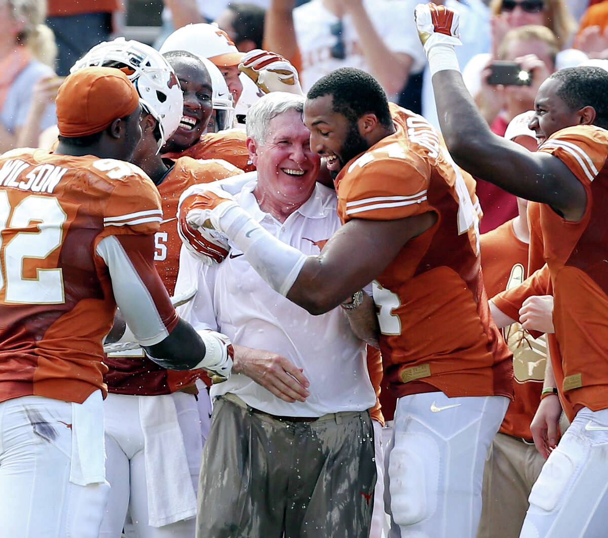 Texas Longhorns' head coach Mack Brown (center) is hugged by Texas Longhorns' Jackson Jeffcoat after being splashed with water near the end of the Red River Rivalry with the Oklahoma Sooners held Saturday Oct. 12, 2013 at Cotton Bowl Stadium in Dallas, Tx. The Longhorns won 36-20.