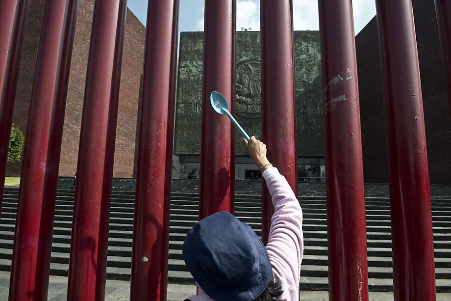 TOPSHOTS A supporter of Andres Manuel Lopez Obrador's left wing movement MORENA hits with a spoon a metalic barrier of the Mexican Congress during a protest against an energy proposal reform in Mexico City on December 11, 2013.  Mexico's Senate approved controversial legislation Wednesday to open the state-controlled energy sector to foreign investment and break the 75-year-old oil monopoly. The bill is the centerpiece of President Enrique Pena Nieto's reform drive, which has included new tax collection, telecommunications and education laws in an effort to revitalize Latin America's second biggest economy.   TOPSHOTS/AFP PHOTO/ Yuri CORTEZYURI CORTEZ/AFP/Getty Images Photo: Yuri Cortez, AFP/Getty Images
