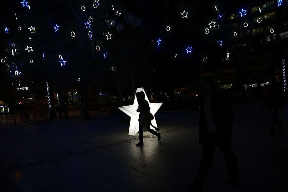 A woman walks at the Christmas decorated Syntagma square opposite the parliament in Athens on December 11, 2013. TOPSHOTS/AFP PHOTO / ARIS MESSINISARIS MESSINIS/AFP/Getty Images Photo: Aris Messinis, AFP/Getty Images
