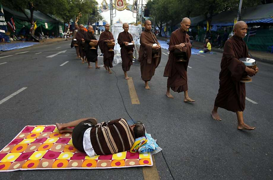 A group of Buddhist monks walk past a sleeping anti-government protester at a protest camp on a road near Government House, where Thai Prime Minister Yingluck Shinawatra's office is located, in Bangkok, Thailand early Wednesday, Dec. 11, 2013. (AP Photo/Greg Baker) Photo: Greg Baker, Associated Press