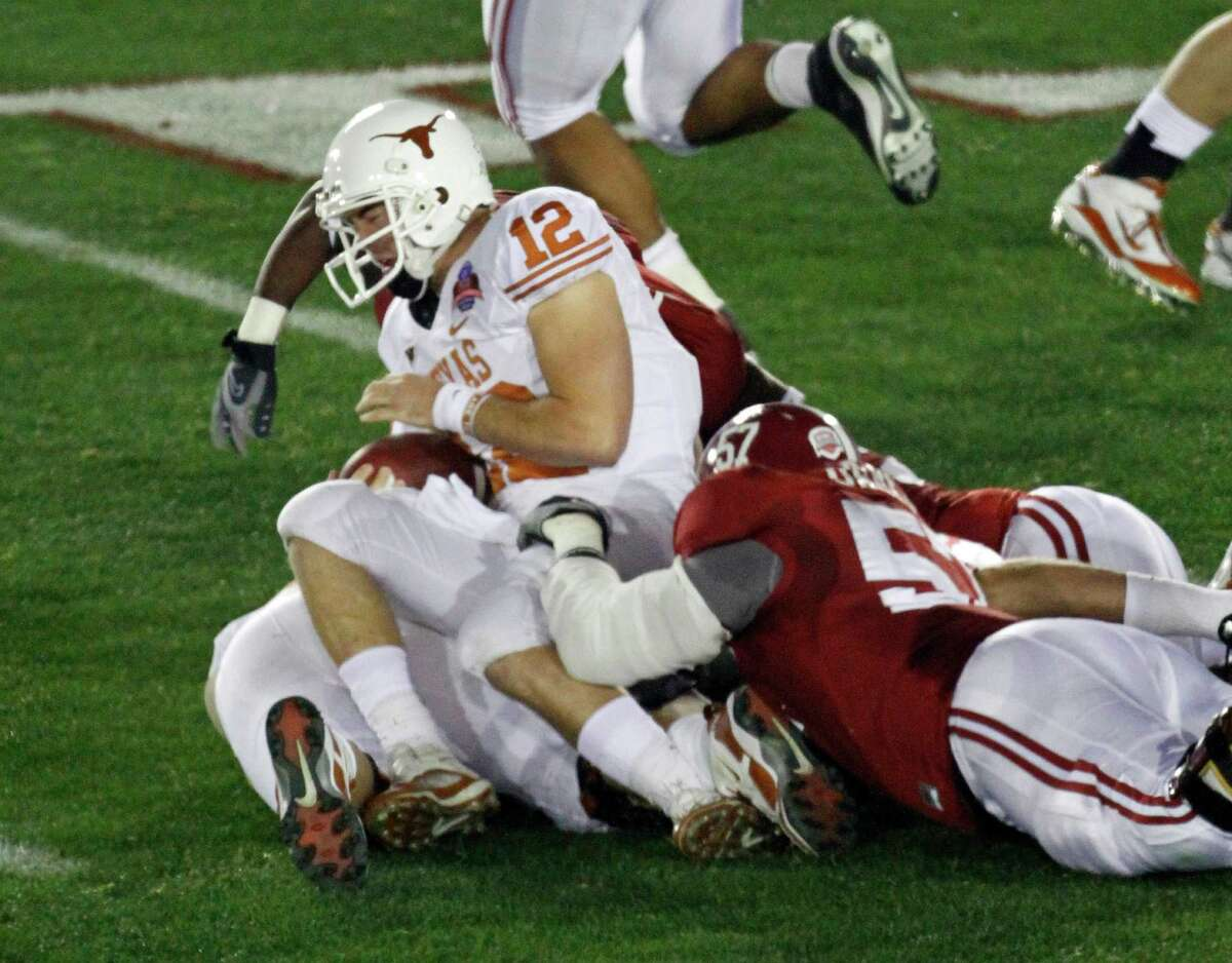 Texas quarterback Colt McCoy (12) is tackled by Alabama defenders during the first quarter of the BCS Championship NCAA college football game in Pasadena, Calif., Thursday, Jan. 7, 2010. McCoy left the game after the play. (AP Photo/Lenny Ignelzi)