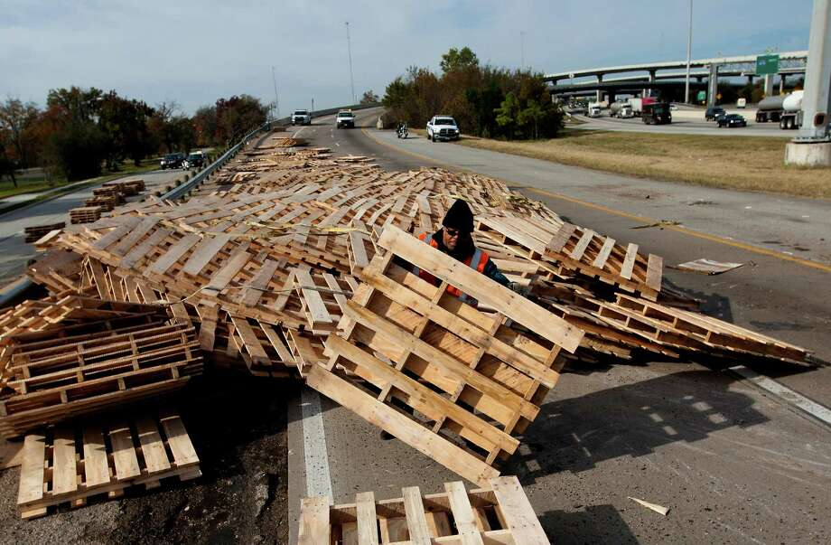 A man labors at the scene of an overturned 18-wheeler that left palettes in the road along the North Loop near the Eastex interchange, Thursday, Dec. 12, 2013, in Houston. The driver came around the curve after exiting heading South on 59 when he swirled around a stalled vehicle. He was not injured and could possibly be cited for a faulty evasive maneuver. Photo: Cody Duty, Houston Chronicle / © 2013 Houston Chronicle