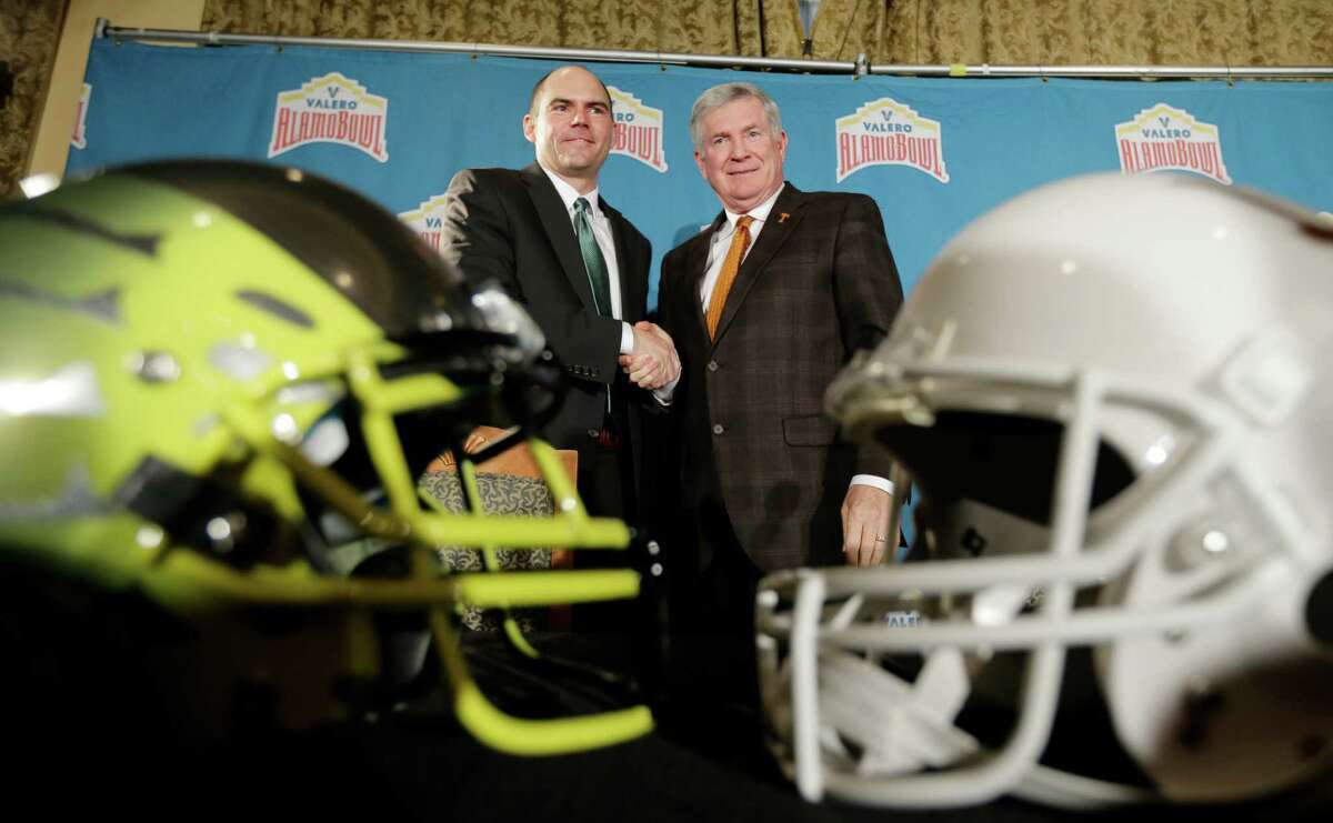 Oregon coach Mark Helfrich, left, and Texas coach Mack Brown, right, pose for a photo following a Valero Alamo Bowl NCAA college football news conference, Thursday, Dec. 12, 2013, in San Antonio. Texas and Oregon will play Dec. 30. (AP Photo/Eric Gay)