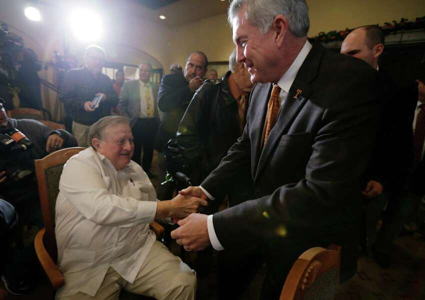 Texas coach Mack Brown, right, reaches out to long-time Texas booster Red McCombs, left, following a Valero Alamo Bowl news conference, Thursday, Dec. 12, 2013, in San Antonio. Texas and Oregon will play in the NCAA college football game Dec. 30. (AP Photo/Eric Gay)