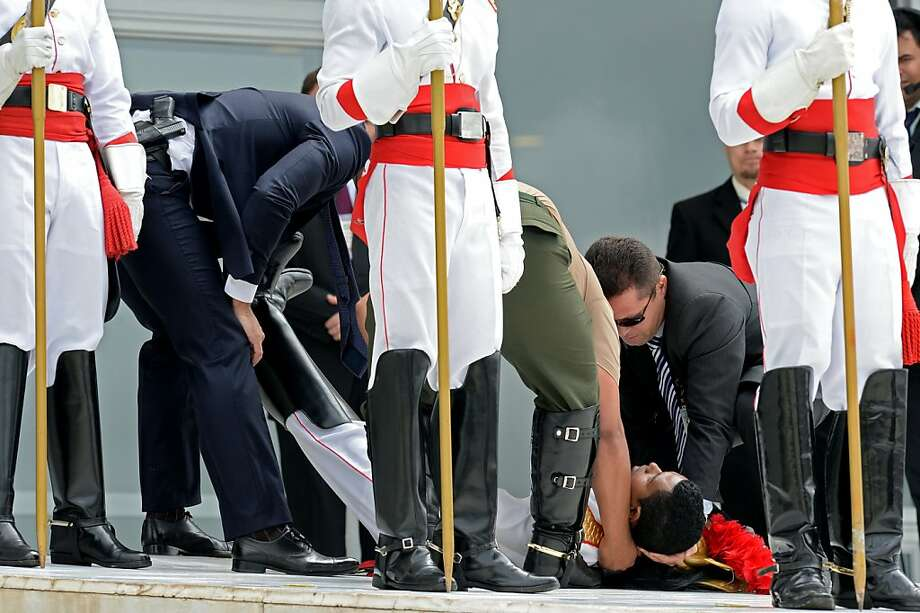 Collapsing at attention:An Honor Guard soldier receives first aid after he fainted in intense heat while waiting for French   President Francois Hollande to arrive at Planalto Palace in Brasilia. Photo: Evaristo Sa, AFP/Getty Images