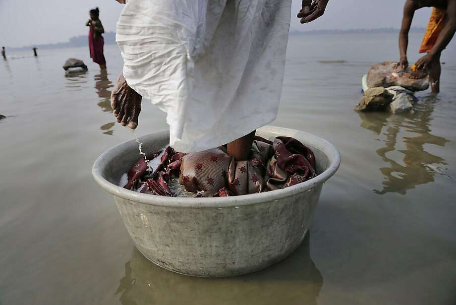 An Indian dhobi washes clothes with his feet in the Brahmaputra River in Gauhati, India, Thursday, Dec. 12, 2013. Dhobis are traditional laundry workers who wash clothes by hand and dry them in the sun, an occupation which has been in existence for generations with a current earning of 65- 81 US cents per cloth.  (AP Photo/Anupam Nath) Photo: Anupam Nath, Associated Press