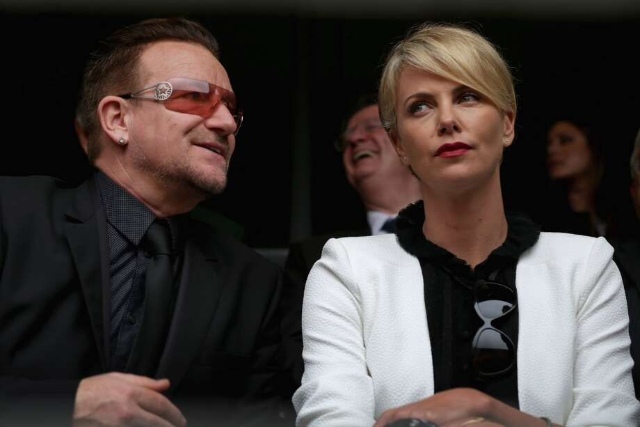 Singer Bono and South African actor Charlize Theron (who does not look amused) arrive for the official memorial service for former South African President Nelson Mandela at FNB Stadium December 10, 2013 in Johannesburg, South Africa. Photo: Chip Somodevilla, Getty Images