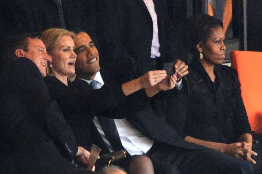 President  Barack Obama (R) and British Prime Minister David Cameron pose for a selfie picture with Denmark's Prime Minister Helle Thorning Schmidt (C) next to US First Lady Michelle Obama (R) during the memorial service of South African former president Nelson Mandela at the FNB Stadium (Soccer City) in Johannesburg on December 10, 2013. Photo: ROBERTO SCHMIDT, AFP/Getty Images