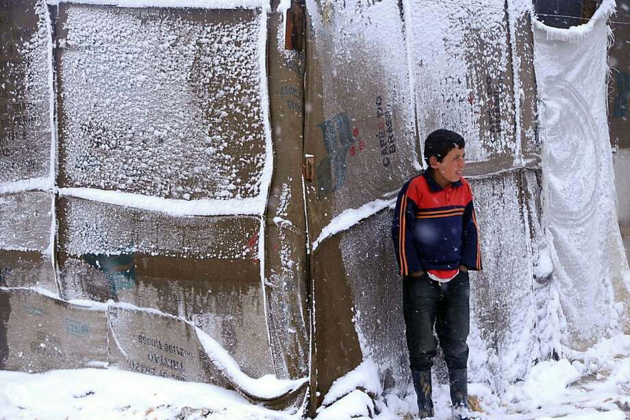 """Weather becomes the enemy:A Syrian refugee boy shivers outside his makeshift tent as a heavy snowstorm batters the Bekaa Valley in eastern Lebanon. The United Nations refugee agency says it was """"extremely concerned"""" for hundreds of thousands of Syrian refugees scattered across the region amid snow, sleet and freezing rain accompanied by high winds. Photo: Uncredited, Associated Press"""