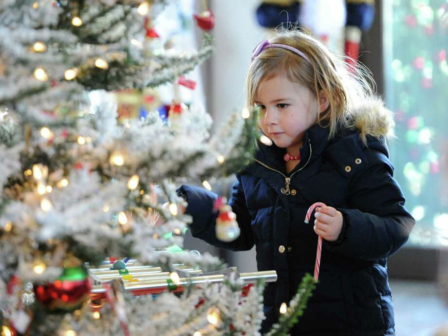 Freya Robertson, 4, of Greenwich, holds a candy cane she received from Santa during a visit to Santa's Workshop at McArdle's Florist & Garden Center in Central Greenwich, Thursday, Dec. 12, 2013. Photo: Bob Luckey / Greenwich Time