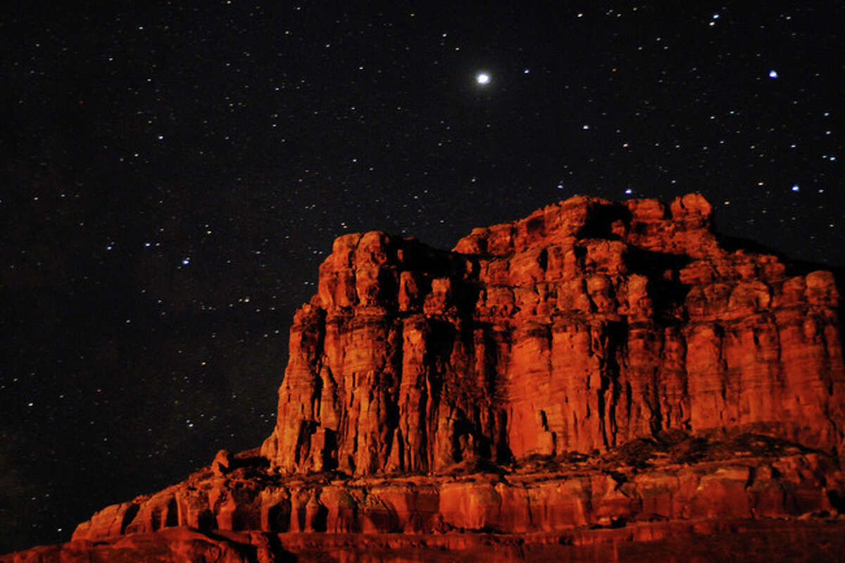 Lake Powell at night (Page, Ariz.) My uncle and I stood with my tripod on the lakeshore behind our houseboat, trying desperately to capture the massive red rock wall before us. It was one of my first lessons in night photography, and it wasn't going great: there just wasn't enough light despite the starry starry sky. I tried over and over, different shutter speeds, using spotlights, nothing worked...too dark. On my last try, I set the shutter speed to a few minutes, as the shutter opened, all of a sudden a houseboat from the next cove over set off fireworks. Their fireworks lit up the entire night sky, and shone their glorious light right on my rock face, resulting in this image.