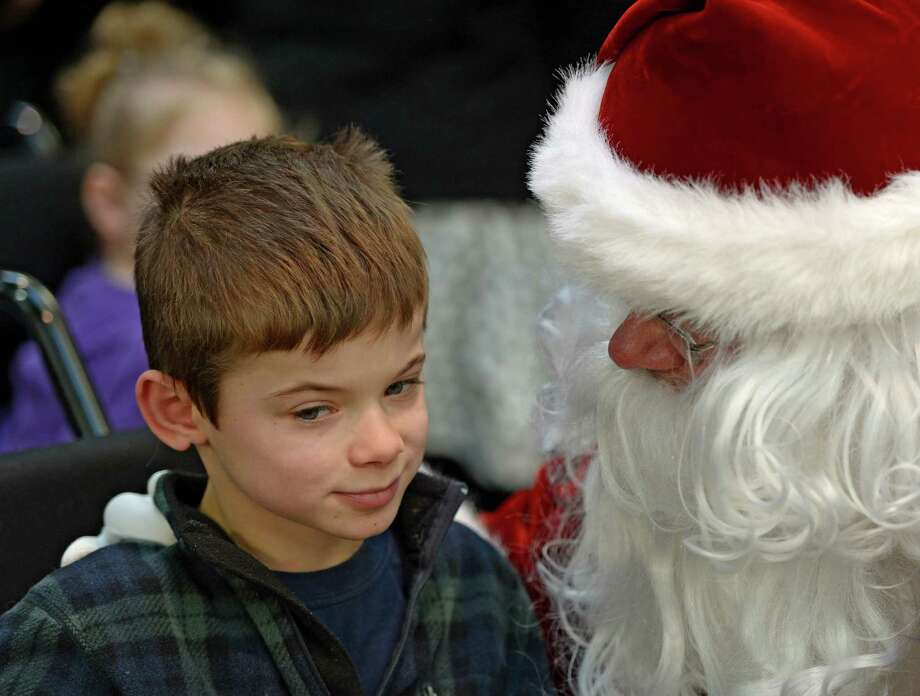 Colden Delaney, left, listens to Santa Claus as members of the Albany Police Athletic League, Albany High School Choir, and Albany police officers deliver gifts for Center for Disability Services students Thursday morning, Dec 12, 2013, at the Langan School and Clover Patch Preschool in Albany, N.Y. (Skip Dickstein/Times Union) Photo: SKIP DICKSTEIN / 00024947A
