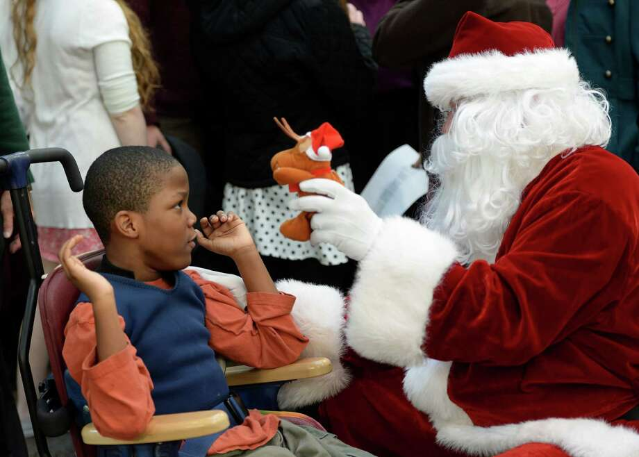 Marquise Sanders, left, is entertained by Santa Claus as members of the Albany Police Athletic League, Albany High School Choir, and Albany Police officers deliver gifts for the Center for Disability Services students Thursday morning, Dec 12, 2013, at the Langan School and Clover Patch Preschool in Albany, N.Y. (Skip Dickstein/Times Union) Photo: SKIP DICKSTEIN / 00024947A