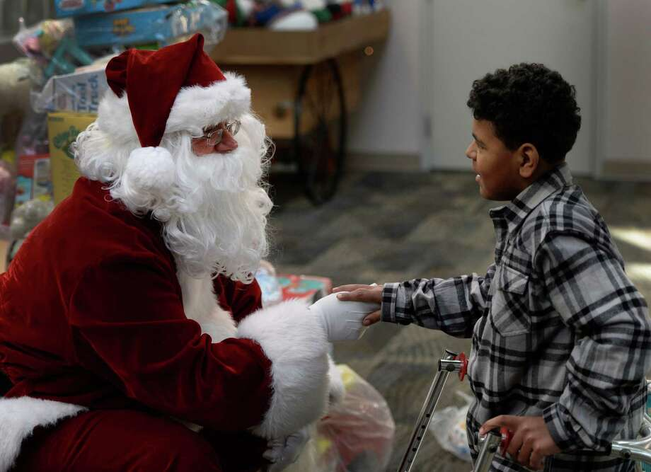 Robert Keene, right, listens to Santa Claus as members of the Albany Police Athletic League, Albany High School Choir, and Albany Police officers deliver gifts for Center for Disability Services students Thursday morning, Dec 12, 2013, at the Langan School and Clover Patch Preschool in Albany, N.Y. (Skip Dickstein/Times Union) Photo: SKIP DICKSTEIN / 00024947A