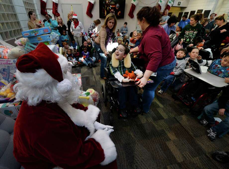 Students are captivated by Santa Claus as members of the Albany Police Athletic League, Albany High School Choir, and Albany Police officers deliver gifts for Center for Disability Services students Thursday morning, Dec 12, 2013, at the Langan School and Clover Patch Preschool in Albany, N.Y.      (Skip Dickstein/Times Union) Photo: SKIP DICKSTEIN / 00024947A