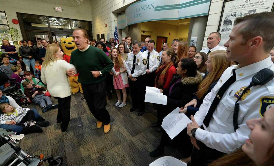 Ann Schneider Costigan dances with PAL executive director Sgt.  (ret.) Leonard Ricchiuti as members of the Albany Police Athletic League, Albany High School Choir, and Albany Police officers deliver gifts for the Center for Disability Services students Thursday morning, Dec 12, 2013, at the Langan School and Clover Patch Preschool in Albany, N.Y. (Skip Dickstein/Times Union) Photo: SKIP DICKSTEIN / 00024947A