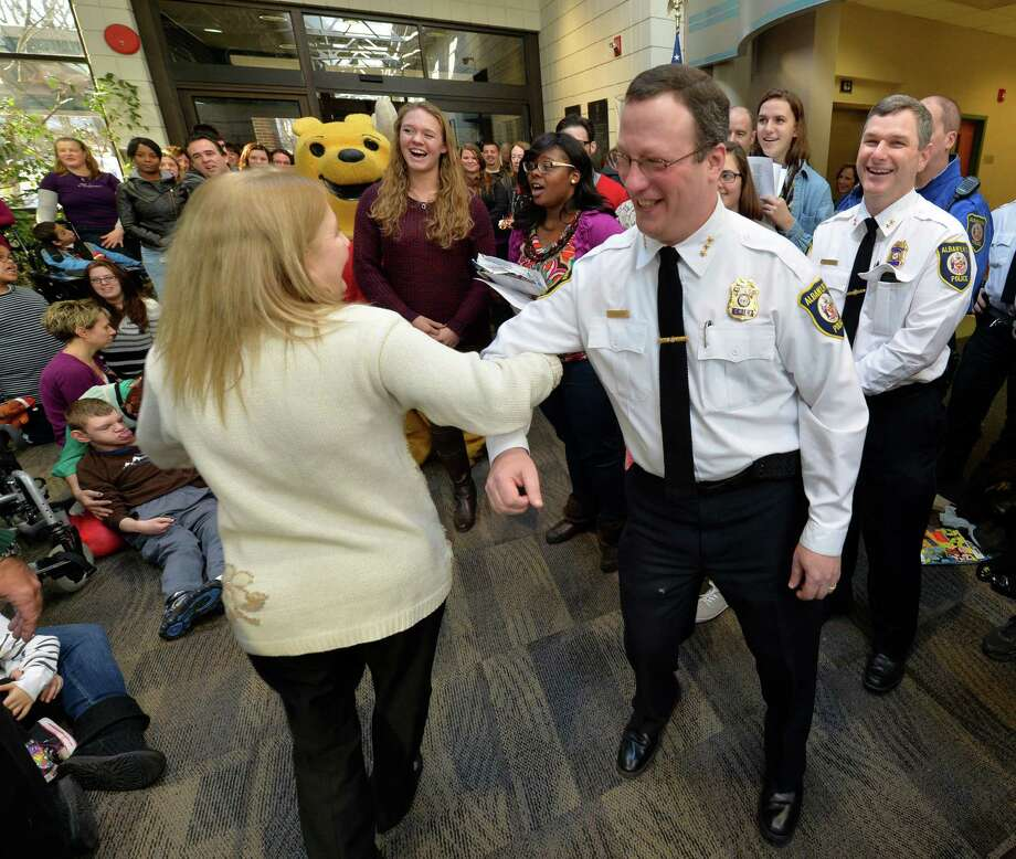 Center for Disability Foundation director Ann Costigan, left, dances with Albany Police Chief Steven Krokoff as members of the Albany Police Athletic League, Albany High School Choir, and Albany Police officers deliver gifts for Center for Disability Services students Thursday morning, Dec 12, 2013, at the Langan School and Clover Patch Preschool in Albany, N.Y. (Skip Dickstein/Times Union) Photo: SKIP DICKSTEIN / 00024947A