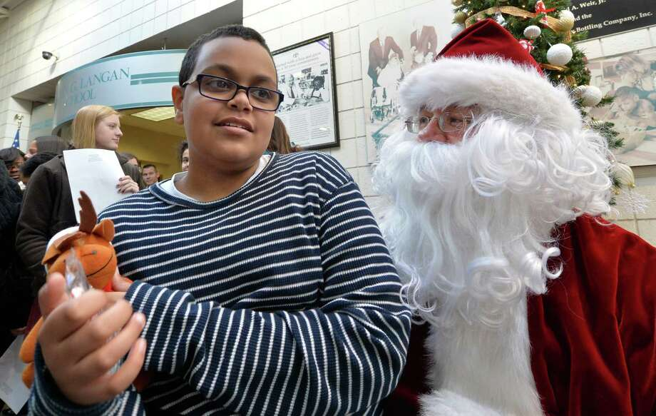 Meki Abdallah, left, listens to Santa Claus as members of the Albany Police Athletic League, Albany High School Choir, and Albany Police officers deliver gifts for the Center for Disability Services students Thursday morning, Dec 12, 2013, at the Langan School and Clover Patch Preschool  in Albany, N.Y.   (Skip Dickstein/Times Union) Photo: SKIP DICKSTEIN / 00024947A