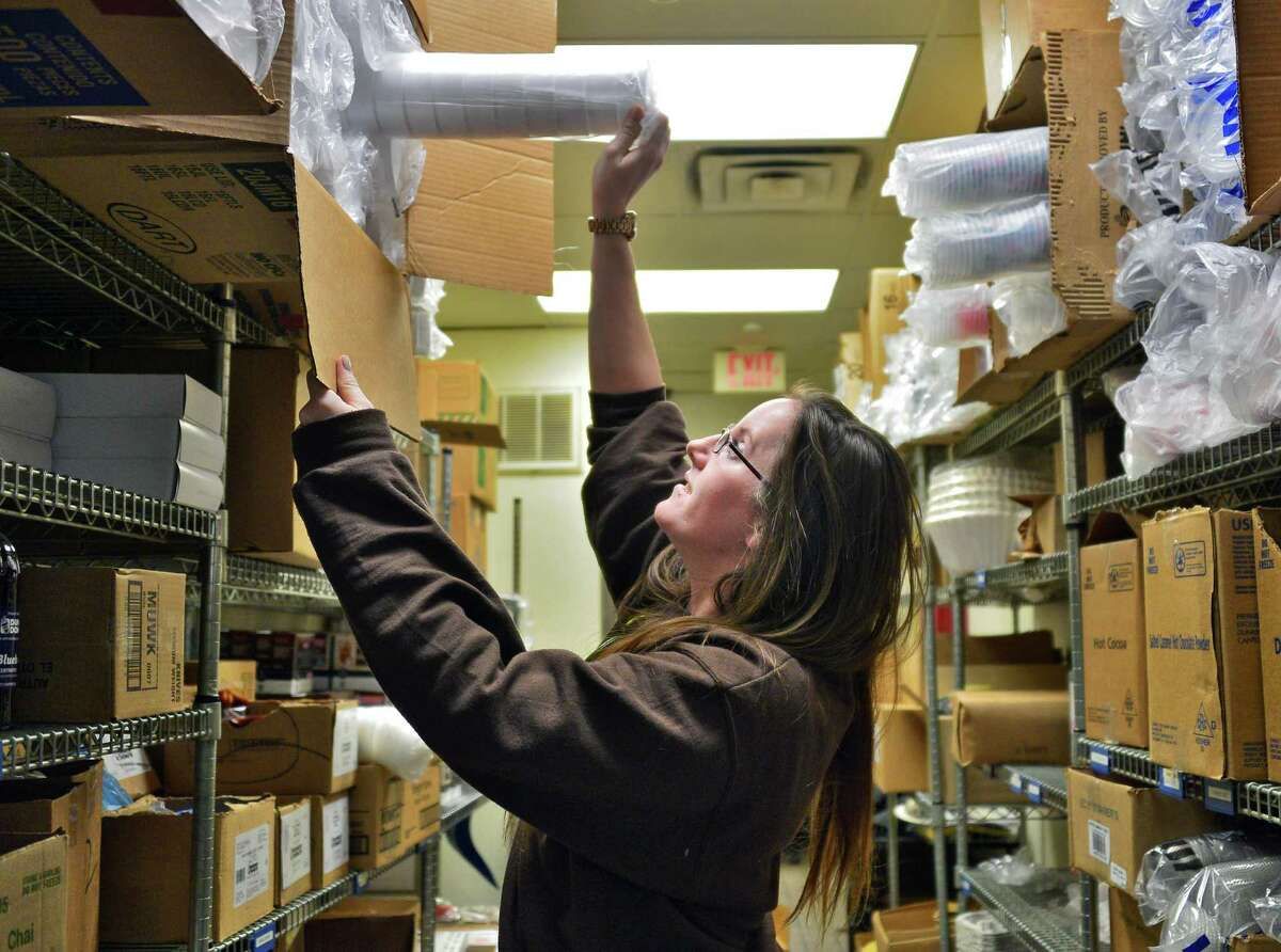 Dunkin' Donuts Western Avenue store manager Meghan Wisner with boxes of Styrofoam coffee cups in their storeroom Thursday, Dec. 12, 2013, in Albany, N.Y. (John Carl D'Annibale / Times Union)
