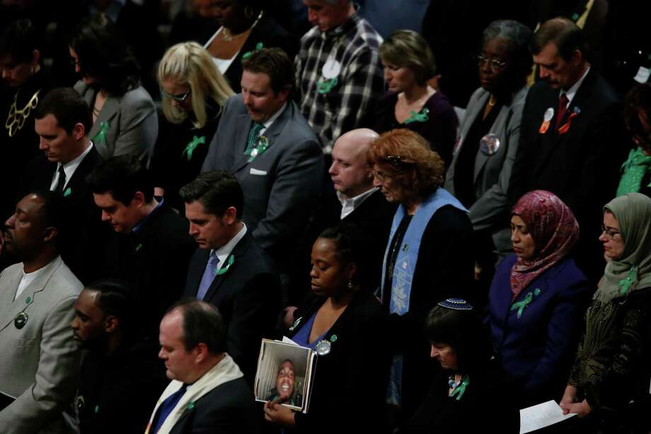 Family members of victims of gun violence stand as they hold a vigil for victims of the shooting at Sandy Hook Elementary School in Newtown, Conn. and other victims of gun violence, Thursday, Dec. 12, 2013, at the National Vigil for Victims of Gun Violence at the National Cathedral in Washington. The one year anniversary of the Newtown, Conn. shootings is December 14. Photo: Charles Dharapak, AP Photo/Charles Dharapak / Associated Press