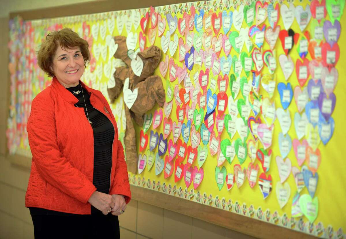 Principal Alana Callahan stands in front of a bulletin board at Park City Magnet School where staff and students have each signed a pledge of kindness inscribed on hearts in memory of Sandy Hook victims.