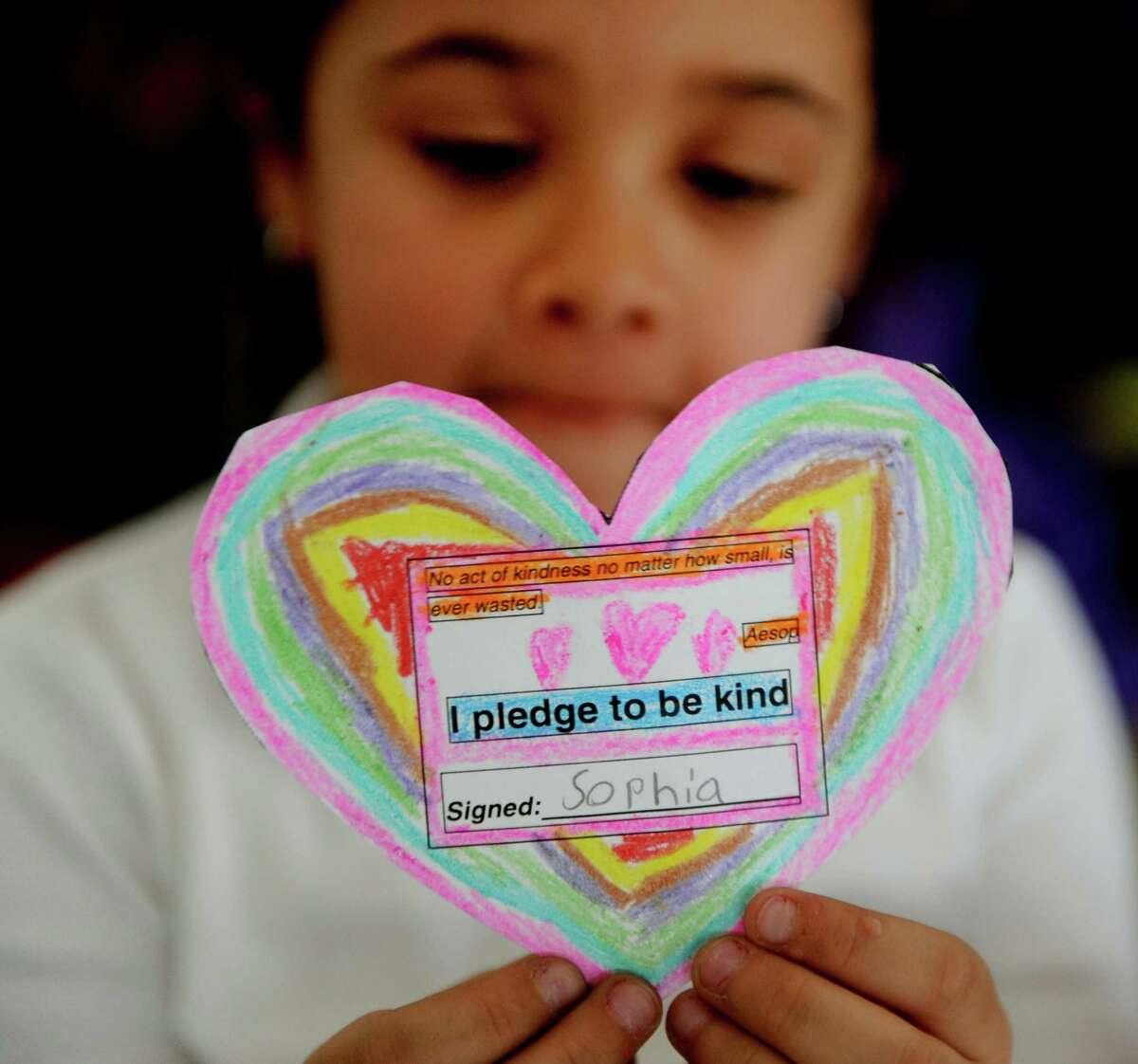 First grade student Sophia Servan holds up her pledge to be kind Thursday, Dec. 12, 2013 at Park City Magnet School. Staff and students at the school have each decorated and signed these hearts in memory of Sandy Hook victims.