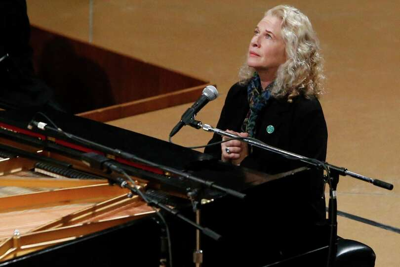 Singer Carole King puts her hands together after performing at a vigil for victims of the shooting a