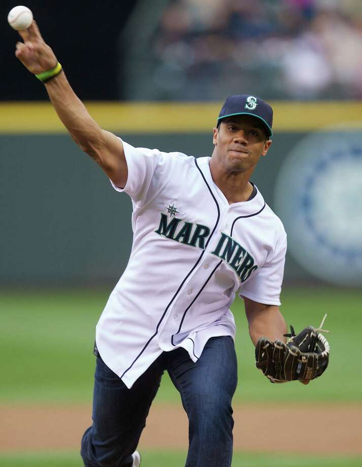 FILE - In this June 7, 2013 file photo, Seattle Seahawks quarterback Russell Wilson throws out the ceremonial first pitch before a baseball game between the Seattle Mariners and the New York Yankees, in Seattle. Wilson has been selected by the Texas Rangers from the Colorado Rockies in the Triple-A portion of baseball's winter meeting draft. The Rangers made the Rule 5 pick Thursday, Dec. 12, 2013. Wilson, who played minor league baseball for parts of two seasons before becoming an NFL star, will be placed on Texas' restricted list. (AP Photo/Stephen Brashear, File) Photo: Stephen Brashear, Associated Press / FR159797 AP
