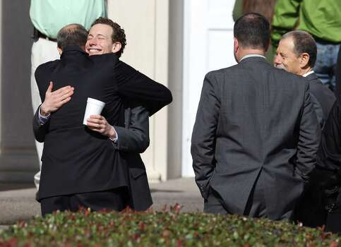 Kris Redus (center), a brother of Cameron Redus, receives a hug in front of Memorial Baptist Church for funeral services for Cameron in Baytown, Texas on Thursday, Dec. 12, 2013. Cameron died of gunshot wounds from a University of Incarnate Word campus policeman last Friday. Family and friends gathered at the church to pay their last respects to the 23-year-old. Photo: Kin Man Hui, San Antonio Express-News / ©2013 San Antonio Express-News