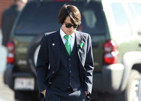 Johnathan Guajardo, a school classmate of Cameron Redus, wears a green tie and ribbon in memory of Redus before a funeral service at Memorial Baptist Church in Baytown, Texas on Thursday, Dec. 12, 2013. Cameron died of gunshot wounds from a University of Incarnate Word campus policeman last Friday. Family and friends gathered at the church to pay their last respects to the 23-year-old. Green was Redus' favorite color and classmates made 700 ribbons to pass out to mourners at the service. Photo: Kin Man Hui, San Antonio Express-News / ©2013 San Antonio Express-News