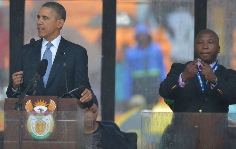 In this picture taken on December 10, 2013 US President Barack Obama delivers a speech next to a sign language interpreter (R) during the memorial service for late South African President Nelson Mandela at Soccer City Stadium in Johannesburg. South Africa's deaf community on December 11, 2013 accused the sign language interpreter at Nelson Mandela's memorial of being a fake, who had merely flapped his arms around during speeches. Mandela, the revered icon of the anti-apartheid struggle in South Africa and one of the towering political figures of the 20th century, died in Johannesburg on December 5 at age 95.  AFP PHOTO / ALEXANDER JOEALEXANDER JOE/AFP/Getty Images Photo: ALEXANDER JOE, AFP/Getty Images