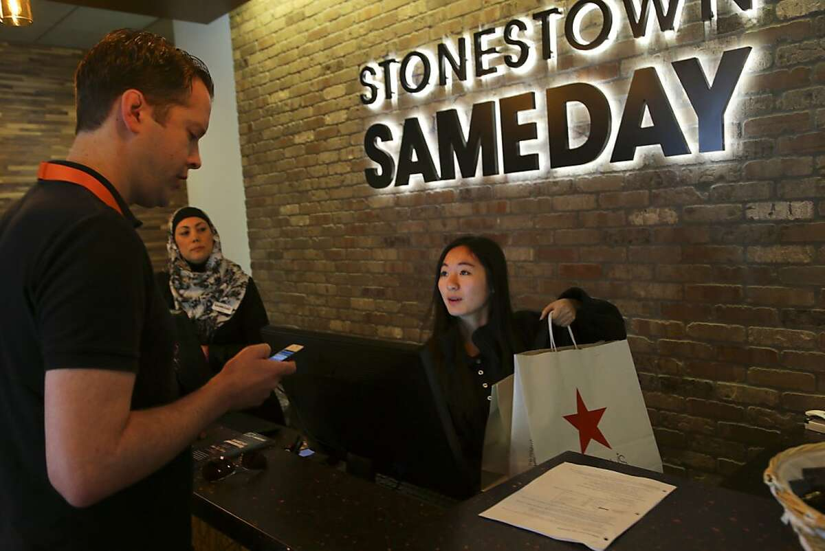 Steve Ahboltin of Deliv, a start-up that uses crowdsourcing to help with same day deliveries, checks a phone app to verify information for packages from Mary Tam at the Stonestown Galleria Mall in San Francisco, Nov. 18, 2013. Services like Deliv use existing stores or �