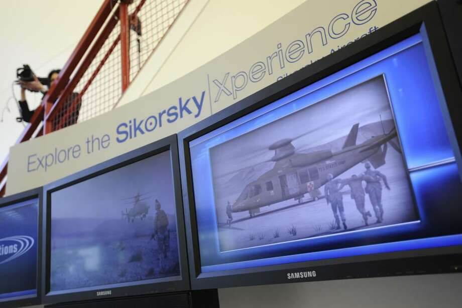 A camera person films attendees at a news event launching Sikorsky Aircraft Corporation's new technology creation business, Sikorsky Innovations, in Hartford, Conn., Monday, Feb. 1, 2010. The Stratford-based helicopter maker and military contractor is launching a $1 billion venture featuring a pilot-less Black Hawk helicopter.(AP Photo/Jessica Hill) Photo: Jessica Hill, AP