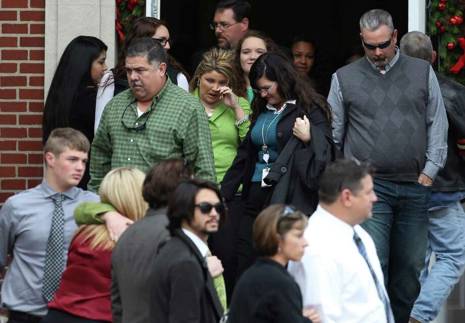 Friends and family of Cameron Redus leave Memorial Baptist Church after the funeral service for Redus in Baytown, Texas on Thursday, Dec. 12, 2013. Redus died of gunshot wounds from a University of Incarnate Word campus policeman last Friday. Family and friends gathered at the church to pay their last respects to the 23-year-old. Green was Redus' favorite color and classmates made 700 ribbons to pass out to mourners at the service. Photo: Kin Man Hui, San Antonio Express-News / ©2013 San Antonio Express-News
