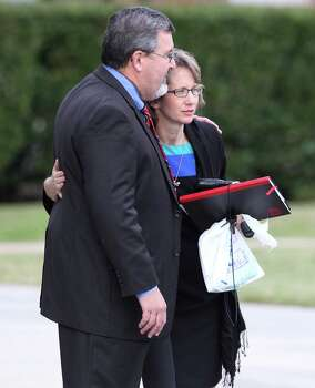 Valerie Redus, mother of Cameron Redus, receives a hug from close family friend Mark Hall after a funeral service for Cameron at Memorial Baptist Church in Baytown, Texas on Thursday, Dec. 12, 2013. Cameron died of gunshot wounds from a University of Incarnate Word campus policeman last Friday. Family and friends gathered at the church to pay their last respects to the 23-year-old. Green was Redus' favorite color and classmates made 700 ribbons to pass out to mourners at the service. Photo: Kin Man Hui, San Antonio Express-News / ©2013 San Antonio Express-News