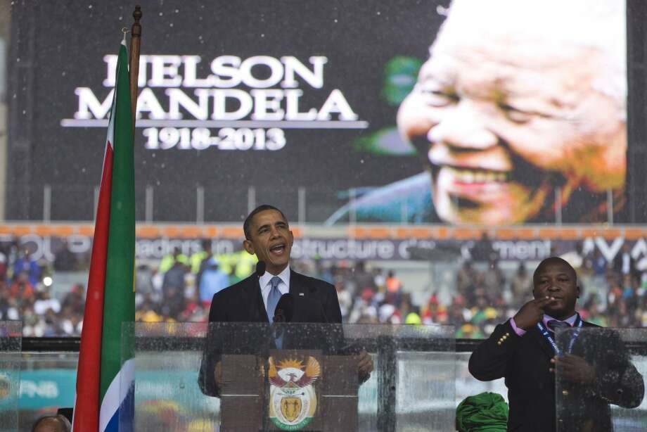 "President Barack Obama delivers his speech next to a sign language interpreter during a memorial service at FNB Stadium in honor of Nelson Mandela on Tuesday, Dec. 10, 2013 in Soweto, near Johannesburg. The national director of the Deaf Federation of South Africa says a man who provided sign language interpretation on stage for Nelson Mandela's memorial service in a soccer stadium was a ""fake.""(AP Photo/ Evan Vucci) Photo: Evan Vucci, Associated Press"