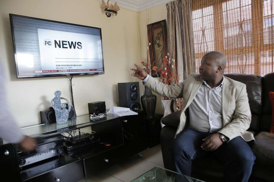 Thamsanqa Jantjie looks around at a television at his home during an interview with the Associated Press in Johannesburg, South Africa,Thursday, Dec. 12, 2013. Jantjie, the man accused of faking sign interpretation next to world leaders at Nelson Mandela's memorial, told a local newspaper that he was hallucinating and hearing voices. (AP Photo/Tsvangirayi Mukwazhi) Photo: Tsvangirayi Mukwazhi, Associated Press