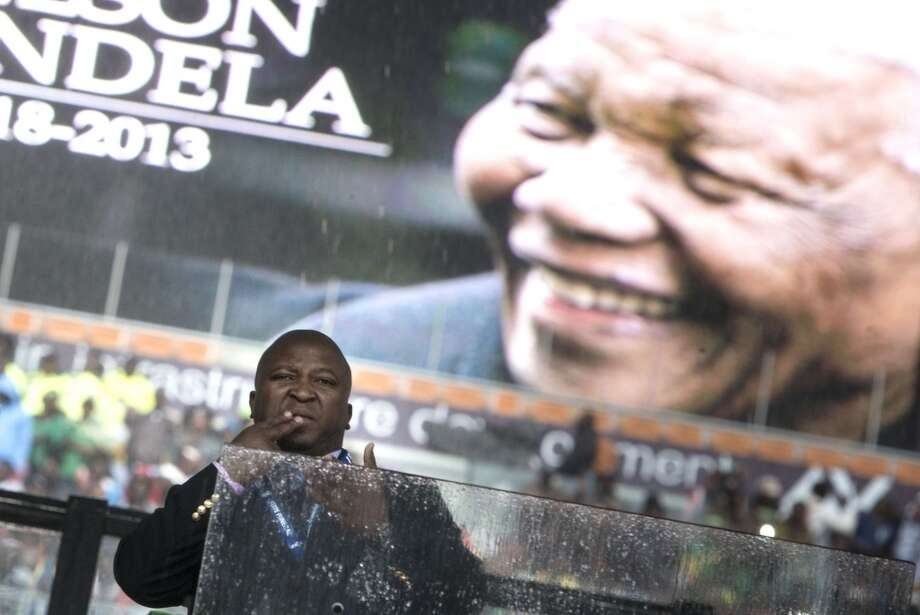 "A sign language interpreter during the memorial service at FNB Stadium December 10, 2013 in Johannesburg, South Africa.  The interpreter was accused ob December 11, 2013, of being a fake who merely flapped his arms around during speeches. ""He's a complete fraud,"" Cara Loening, director of Sign Language Education and Development in Cape Town told AFP. ""He wasn't even doing anything, There was not one sign there. Nothing. He was literally flapping his arms around."" The interpreter, who translated eulogies including those of US President Barack Obama and Mandela's grandchildren, looked as if he was ""trying to swat a few flies away from his face and his head"". ""The deaf community in South Africa are completely outraged and nobody knows who he is,"" said Loening.   AFP PHOTO/Brendan SMIALOWSKIBRENDAN SMIALOWSKI/AFP/Getty Images Photo: BRENDAN SMIALOWSKI, AFP/Getty Images"