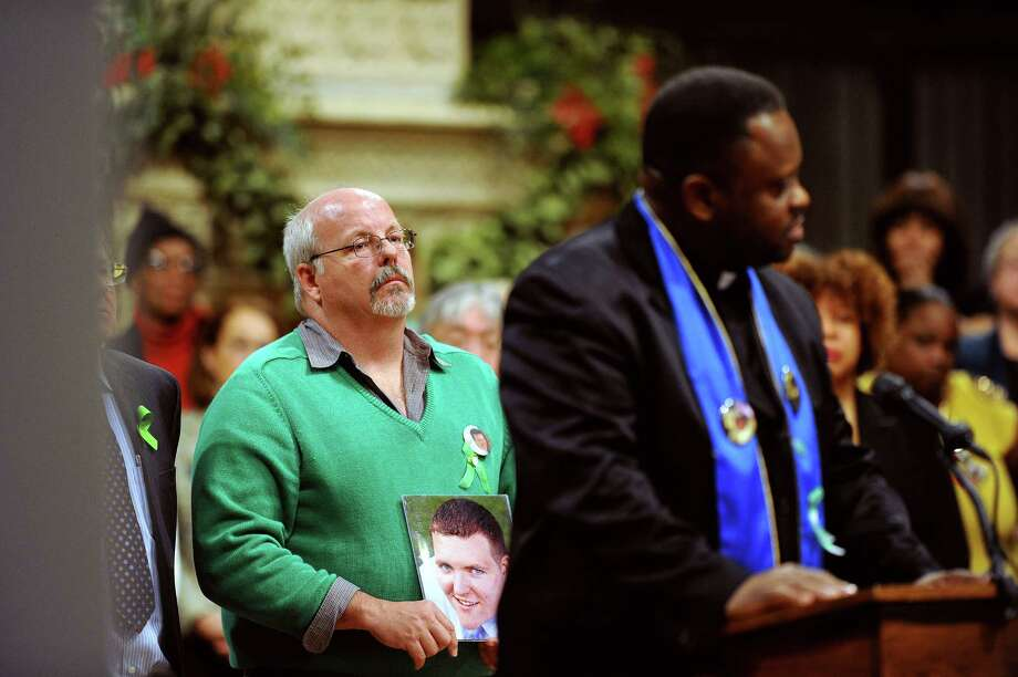 Tom Sullivan, left, holds a photograph of his son, Alex Sullivan, during a National Vigil for Victims of Gun Violence just prior to the first anniversary marking the Sandy Hook Elementary School mass shooting at the National Cathedral on Thursday, Dec. 12, 2013, in Washington. Alex was killed in the Aurora, Colo., movie theater shooting. Members of the Newtown, Conn., community, including the parent of a teacher killed in a school massacre a year ago, gathered for the vigil to remember those who lost their lives because of gun violence. Photo: Matt McClain,  Matt McClain, Pool / Associated Press