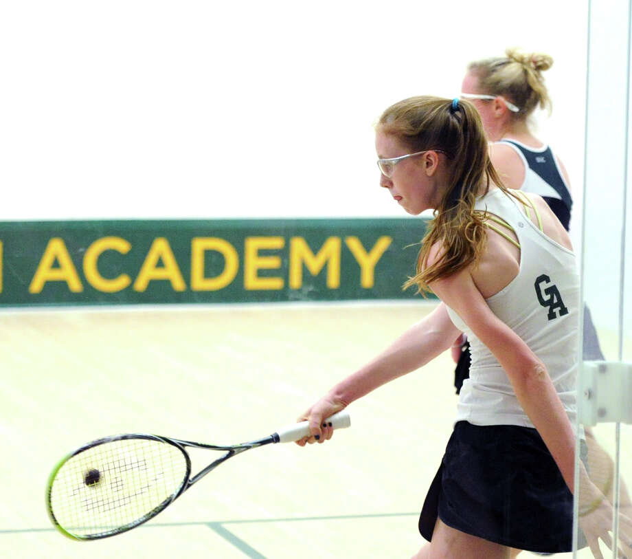 At left, Haley Scott of Greenwich Academy hits in the match she won over Madison Miles of Convent of the Sacred Heart during the high school squash match between Greenwich Academy and Convent of the Sacred Heart at Greenwich Academy, Thursday, Dec. 12, 2013. Photo: Bob Luckey / Greenwich Time