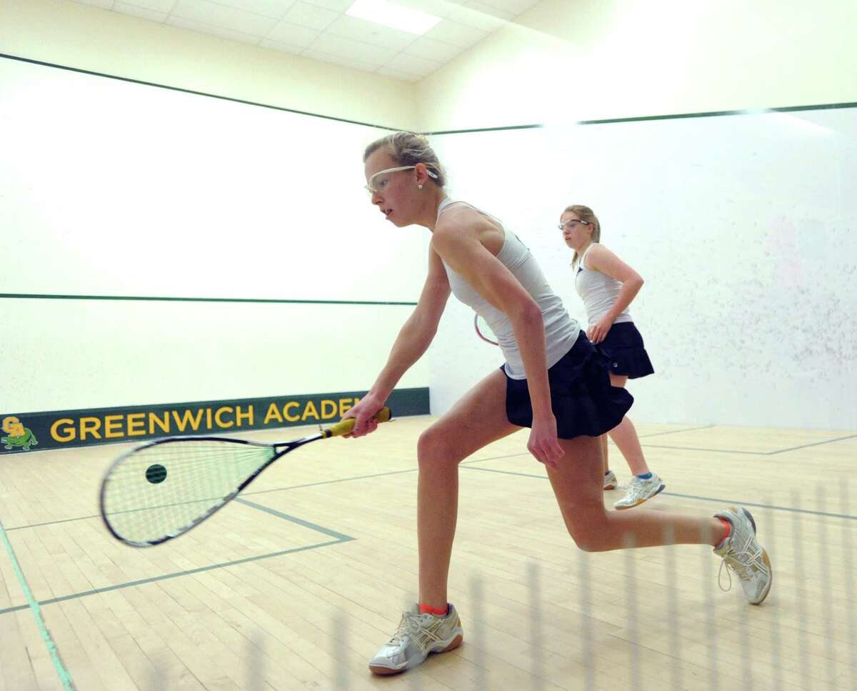 At left, Emme Leonard of Greenwich Academy hits during the match she won against Mary Grace Henry of Conent of the Sacred Heart during the high school squash match between Greenwich Academy and Convent of the Sacred Heart at Greenwich Academy, Thursday, Dec. 12, 2013.
