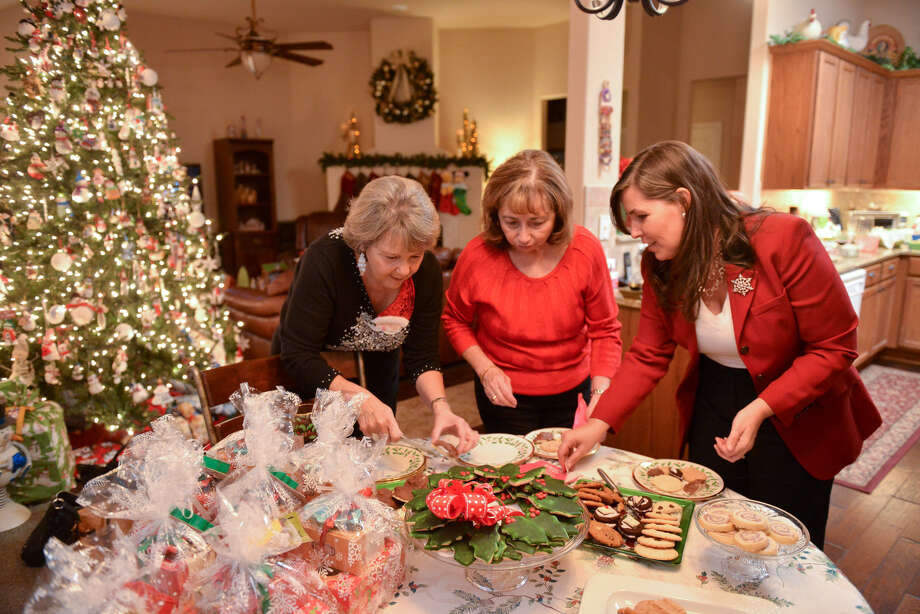 Mary Parish (from left), Kimberly Chumbley and Lori Skinner taste cookies during their annual cookie swap  at their monthly Pokeno gathering. Photo: Photos By Robin Jerstad / For The Express-News