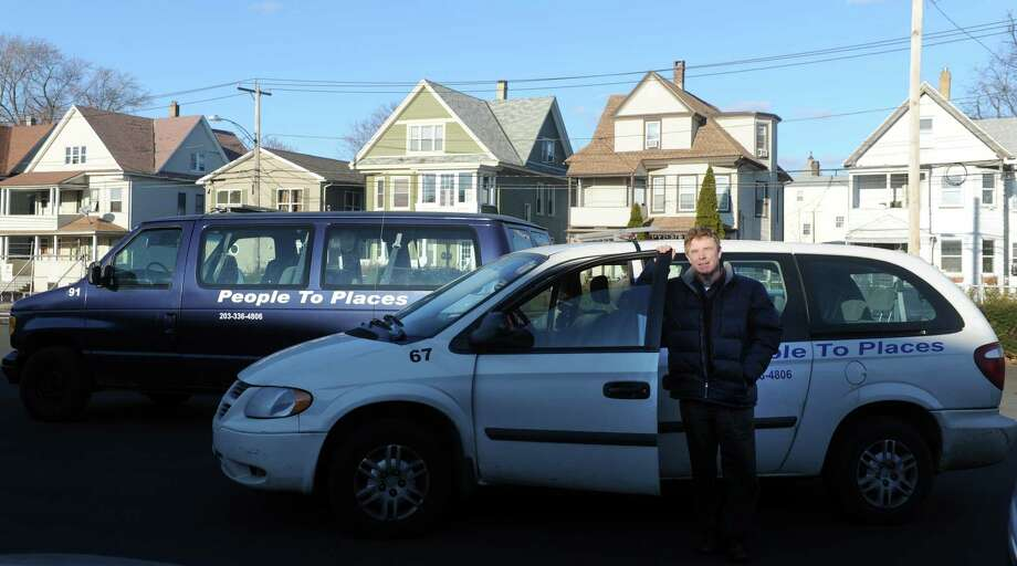 General Manager Brian Williams stands on the lot in Bridgeport, Conn. with People To Places Inc. vans still in operation Thursday, Dec. 12, 2013.  A federal inspection found issues with some of the larger vehicles in the fleet and Williams said those are now out of operation and up for sale. Photo: Autumn Driscoll / Connecticut Post